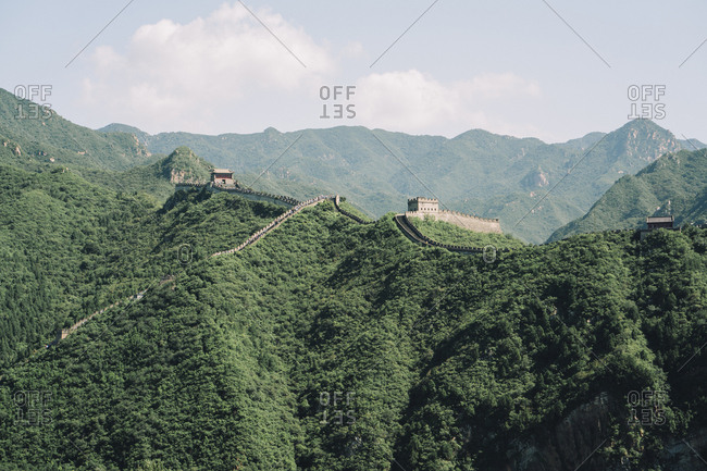 Great Wall of China on green mountain against sky during sunny day