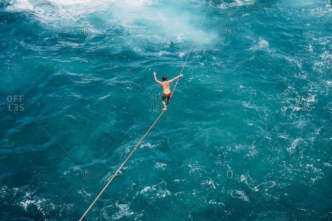 High angle view of carefree young man practicing slacklining over sea