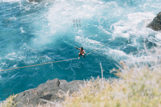 High angle view of young man practicing slacklining over sea