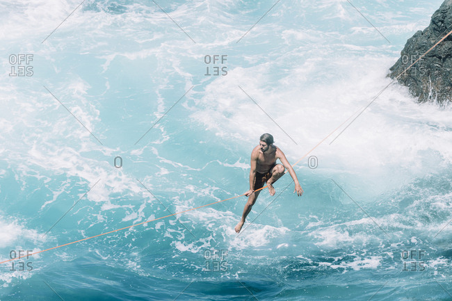 High angle view of carefree young man slacklining on rope over sea during sunny day