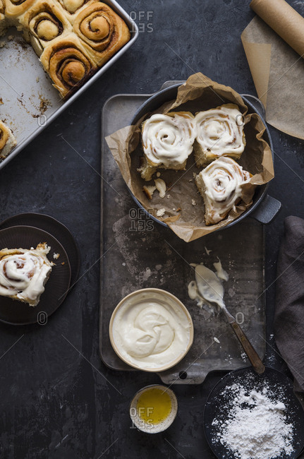 High angle view of cinnamon buns with cream and flour on table