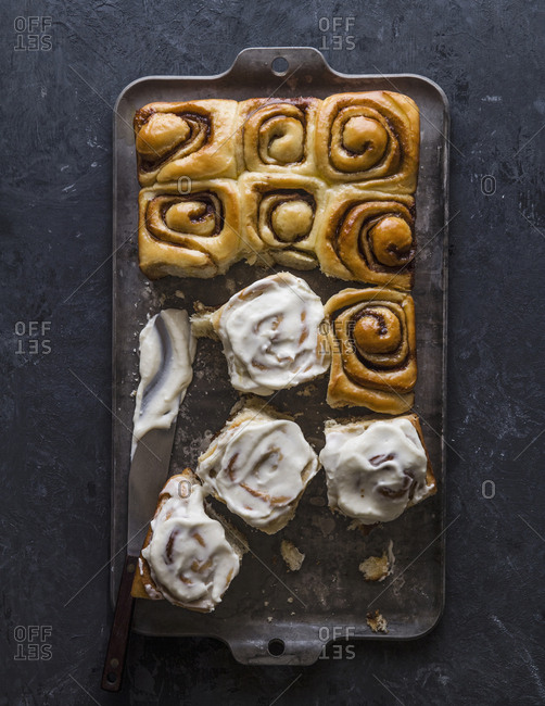 High angle view of cinnamon buns with cream in baking sheet on table