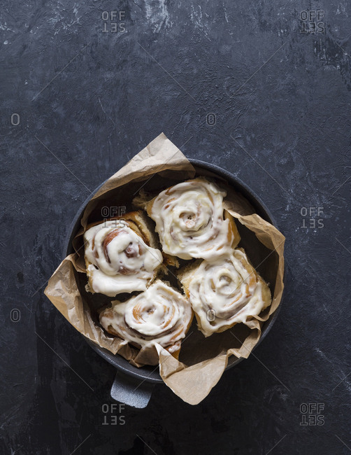 High angle view of cinnamon buns with cream in bowl on table