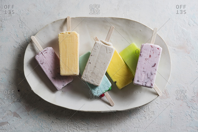 Overhead view of colorful popsicles in plate on table