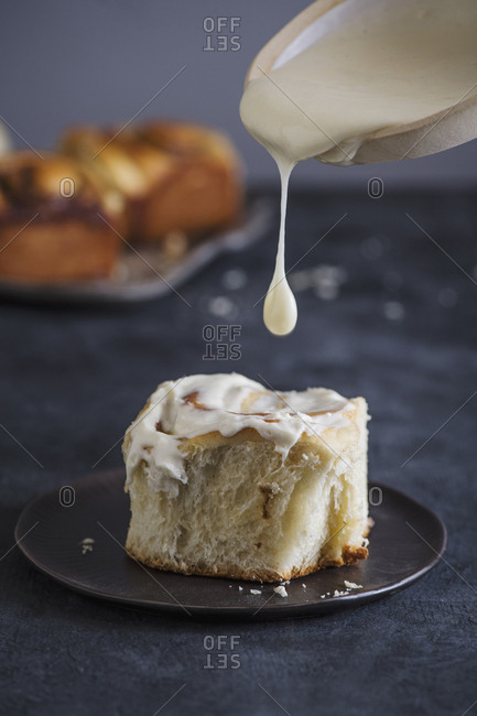 Close-up of cream pouring on cinnamon bun in plate on table