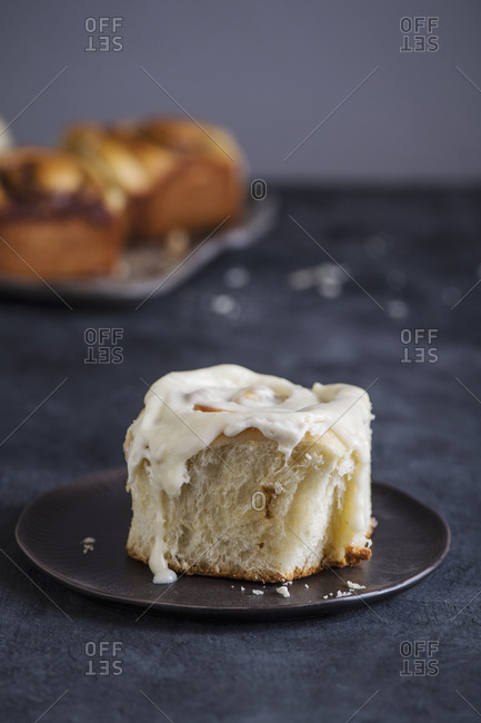Overhead view of cinnamon bun with cream served in plate on table