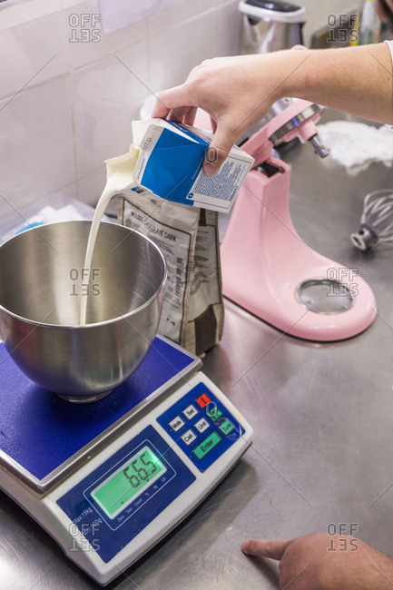 Cropped hands of male baker pouring milk in mixing bowl on weight scale at laboratory
