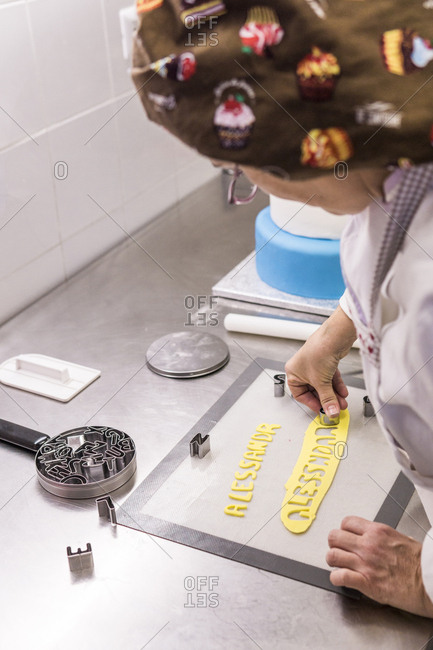 Side view of female baker cutting dough with pastry cutters on kitchen counter in laboratory