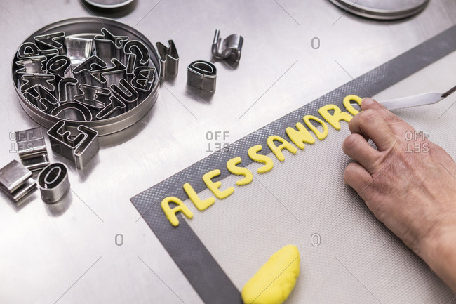 Cropped hand of female baker arranging alphabets made with dough on sheet in kitchen
