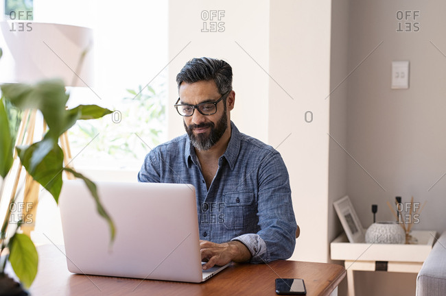 Businessman using laptop computer on wooden table while sitting at home