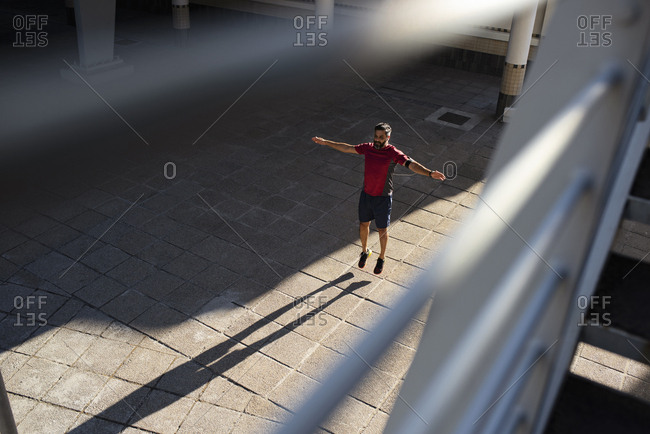 High angle view of confident man with arms outstretched jumping on footpath in city