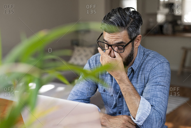 High angle view of stressed businessman with laptop computer sitting at home