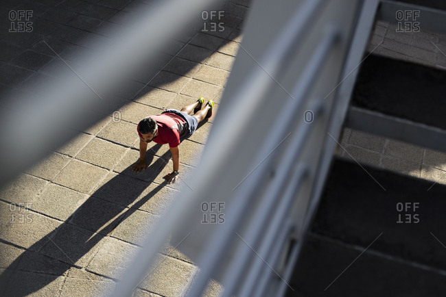 High angle view of confident man doing push-ups on footpath in city