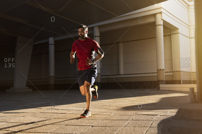 Confident man jogging on footpath against building in city