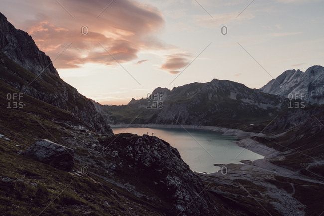 Scenic view of lake amidst mountain ranges against cloudy sky during sunset