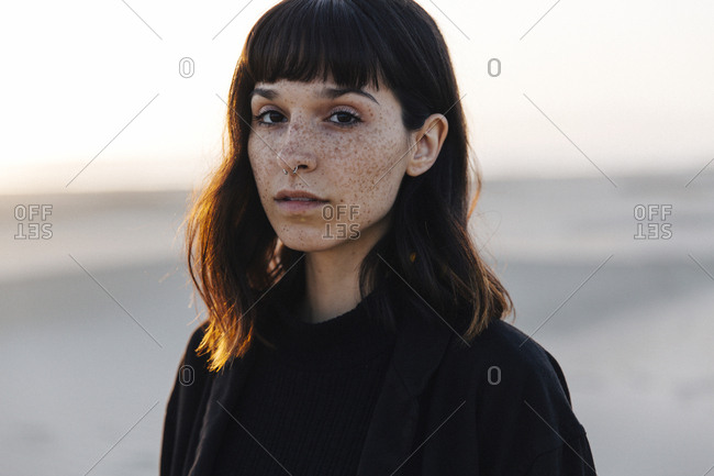 Portrait of woman with freckles standing at beach against clear sky during sunset