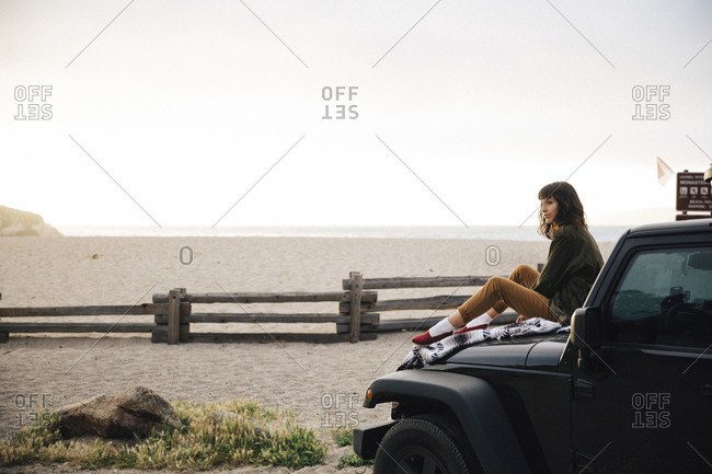 Side view of woman looking away while sitting on off-road vehicle at beach against clear sky during sunset