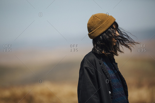 Side view of woman with tousled hair in warm clothing standing against sky during sunny day