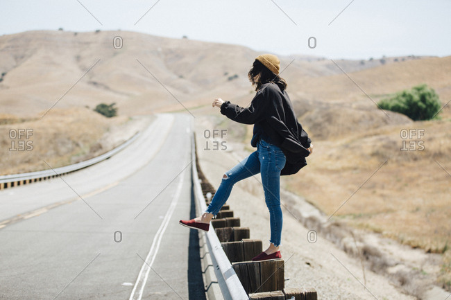 Side view of woman standing on elevated road against clear sky during sunny day