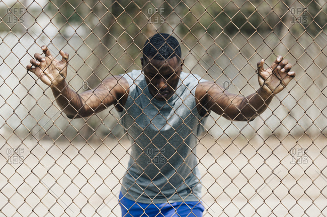 Man exercising on chainlink fence at park