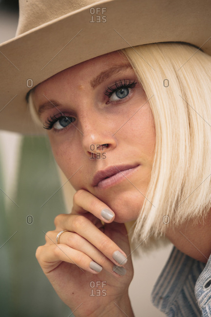 Close-up portrait of confident woman with hand on chin wearing hat while sitting outdoors