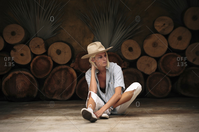 Confident woman wearing beige hat while sitting on floor against decorated wall