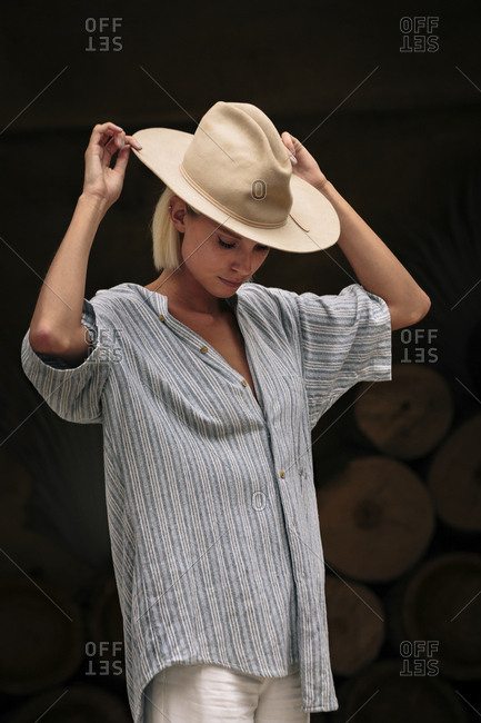Confident woman wearing beige hat while standing against decorated wall
