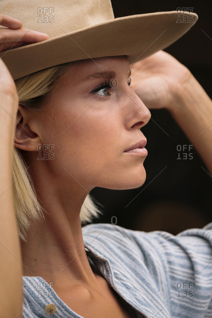 Close-up of thoughtful woman wearing beige hat looking away while standing outdoors