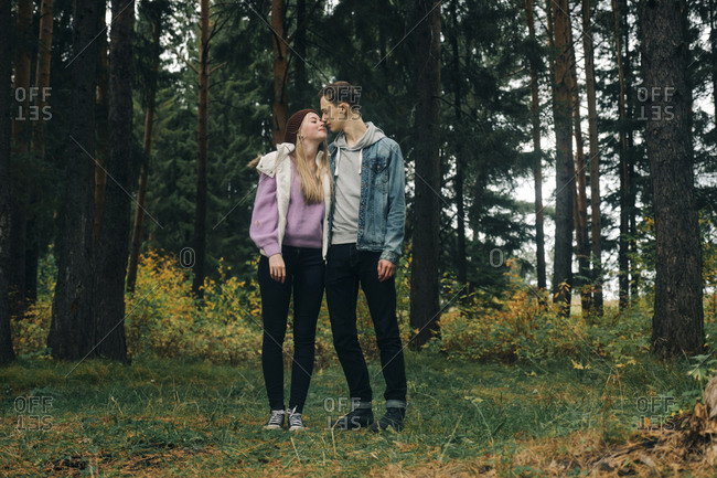 Romantic young couple standing on grassy field against trees in forest