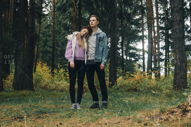young couple standing on grassy field against trees in forest