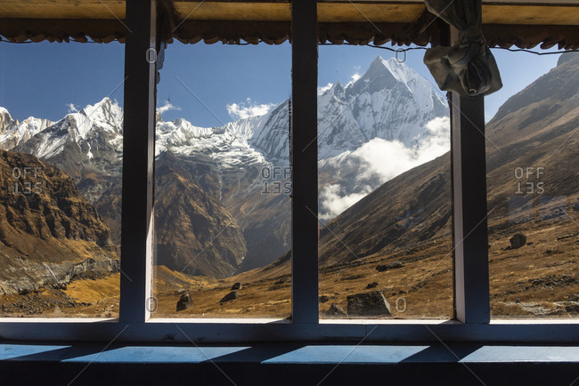 Scenic view of snowcapped mountains against blue sky seen through windows