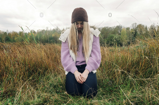 Woman with blond hair kneeling on grassy field against cloudy sky in forest