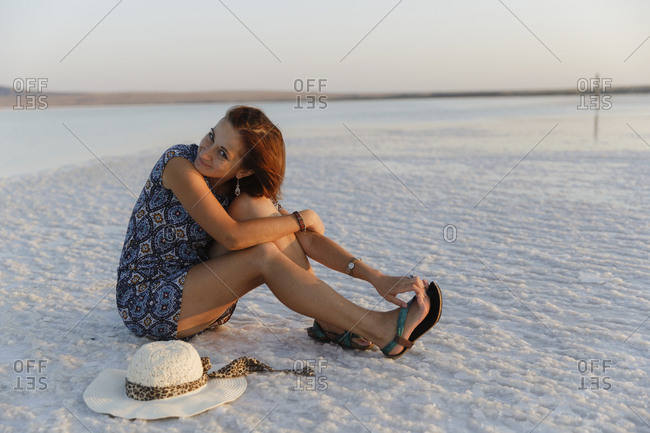 Portrait of woman with hat sitting on salt flat against clear sky during sunset