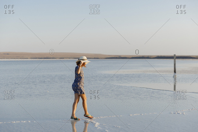 Side view of woman wearing hat walking on salt flat against clear sky during sunset