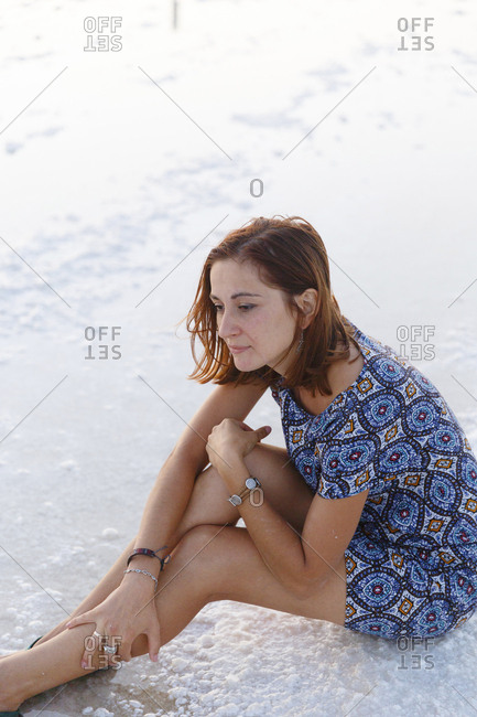 High angle view of woman looking away while sitting on salt flat during sunset