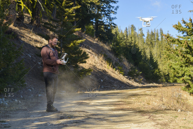 Side view of man flying quadcopter while standing against trees in forest
