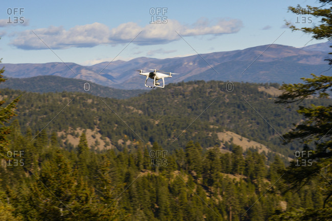 Quadcopter flying over mountains against sky during sunny day