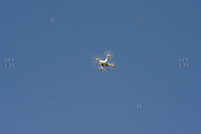Low angle view of quadcopter flying against clear blue sky during sunny day