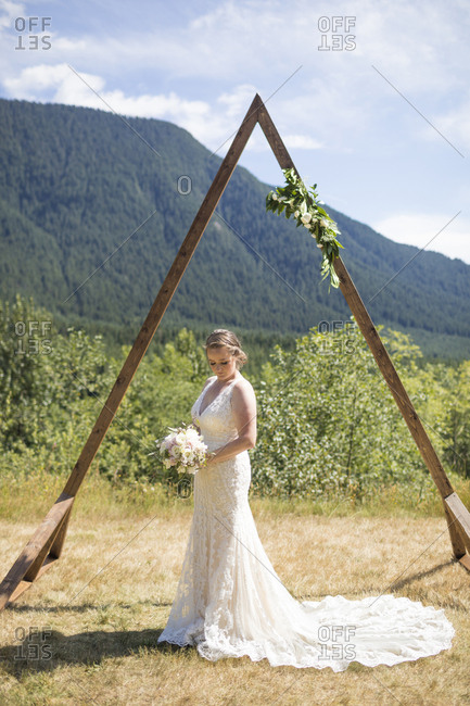 Bride holding bouquet while standing on field against mountain during sunny day in wedding ceremony