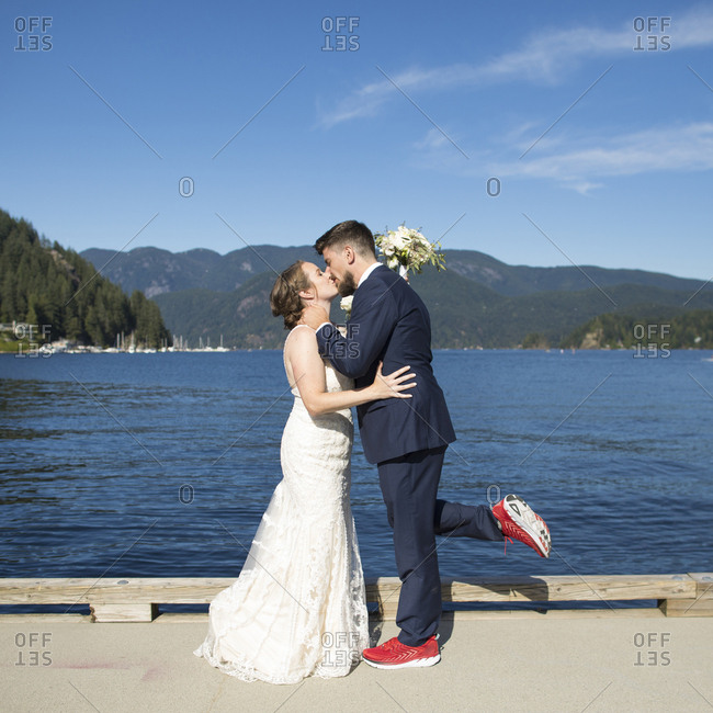 Side view of newlywed couple kissing while standing by lake against blue sky