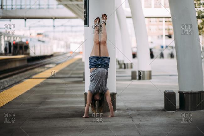 Girl doing handstand at railroad station platform