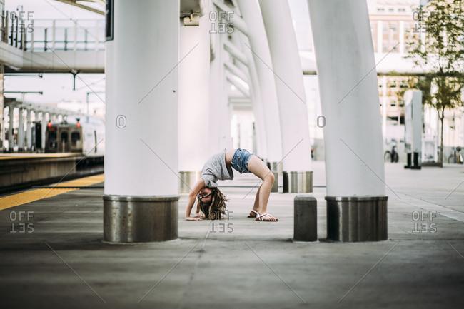 Side view of girl bending over backwards at railroad station platform