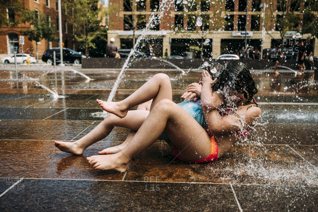 Happy sisters wearing swimwear playing with fountain water against buildings in city