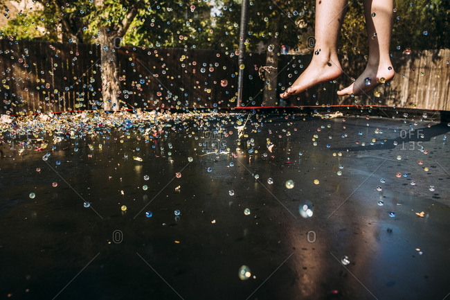 Low section of girl jumping on trampoline during sunny day