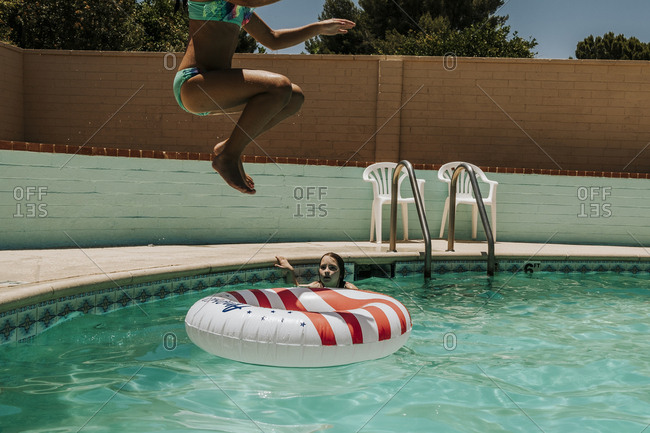 Girl with inflatable ring looking at woman diving in swimming pool during sunny day