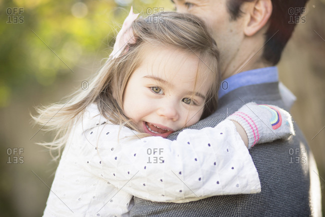 Side view of father carrying cute daughter while standing in yard
