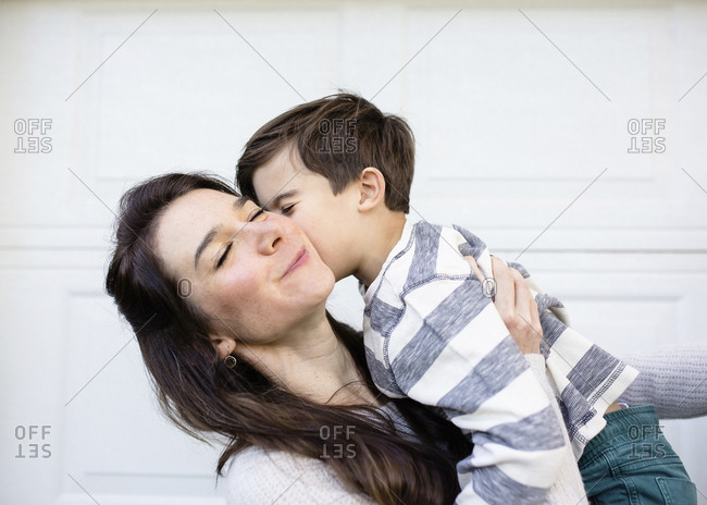 Son kissing happy mother on cheek against wall in yard