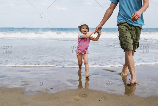 Low section of father holding cute daughter's hands while walking at beach against sky