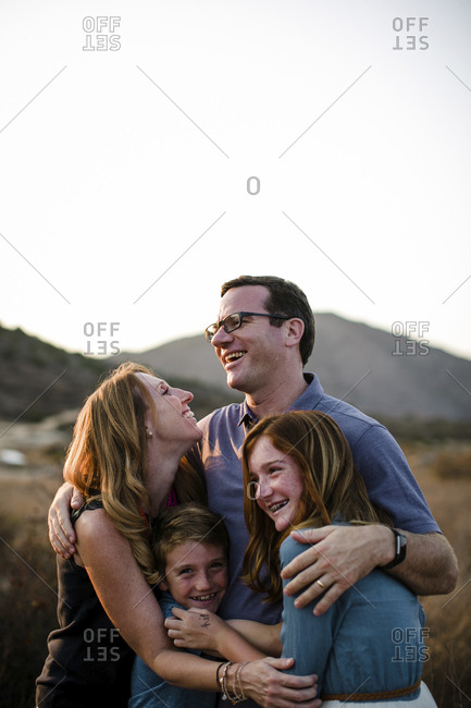 Happy loving family embracing while standing together on field against sky during sunset