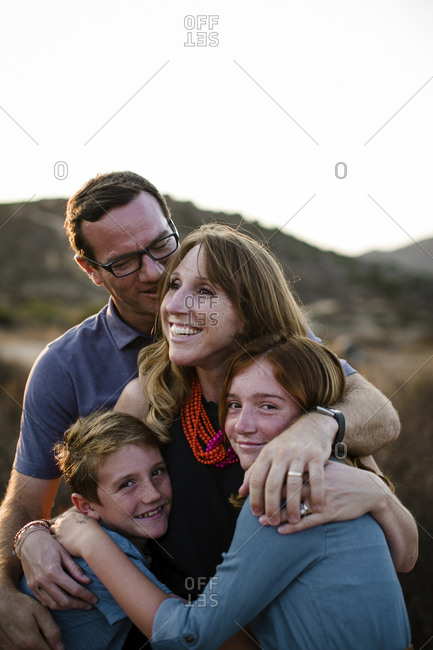 Portrait of happy siblings with parents standing on field during sunset